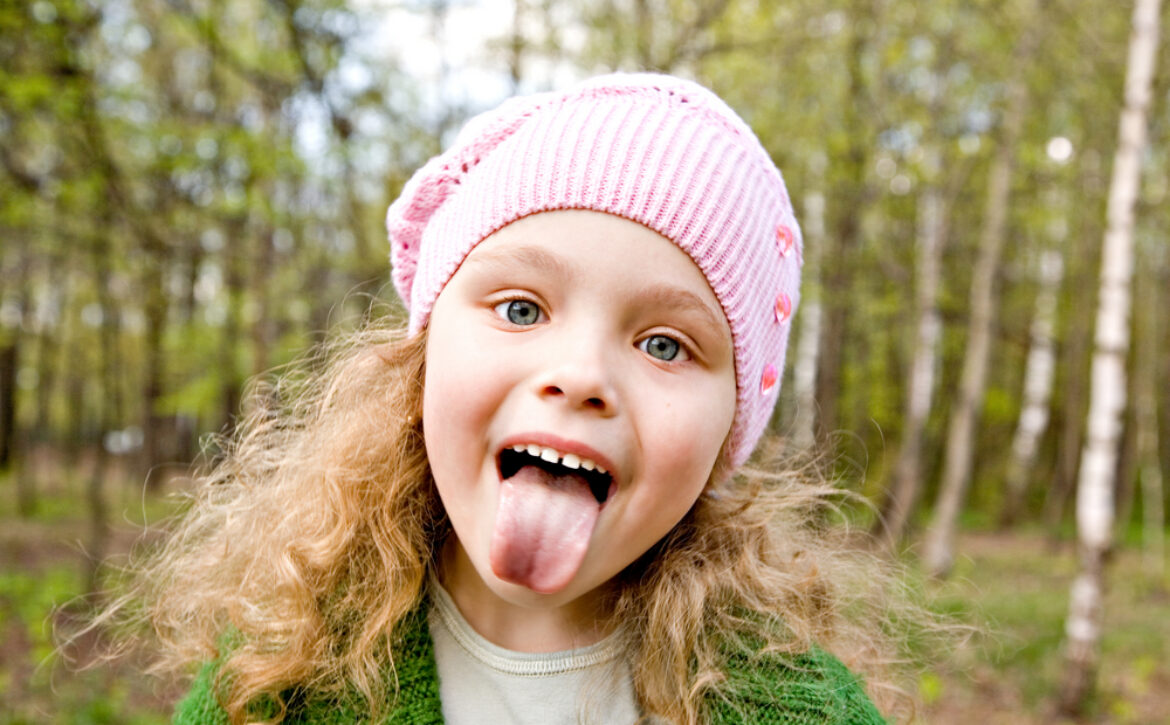 Cheerful,Little,Girl,In,A,Pink,Cap,Puts,Out,The